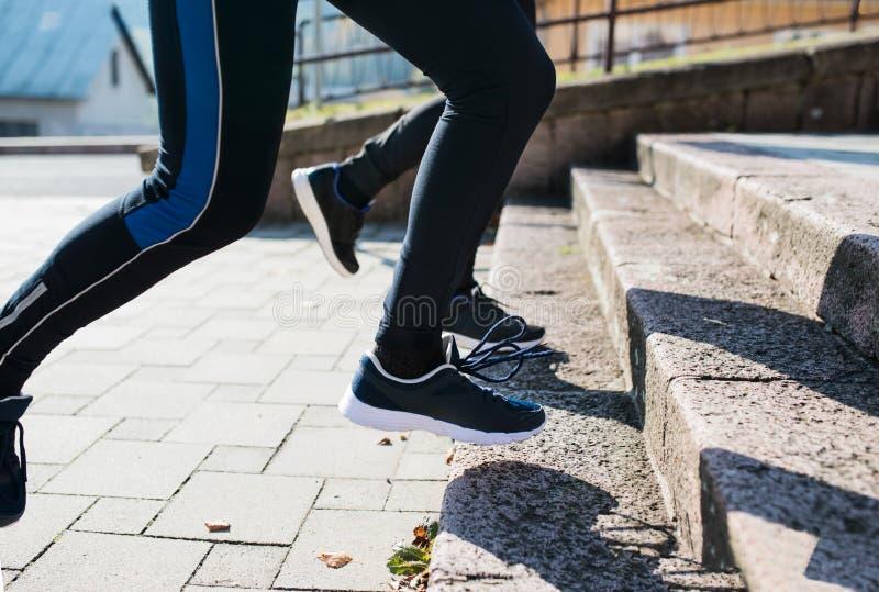 Atletas irreconocibles que corren en las escaleras en día soleado del otoño imagen de archivo libre de regalías