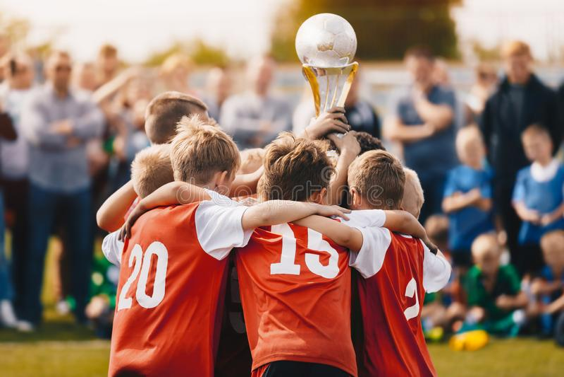 Atletas jovenes de los deportes Team Holding Winning Trophy de la escuela Equipo de deporte del campeón de los niños Muchachos qu imagen de archivo libre de regalías
