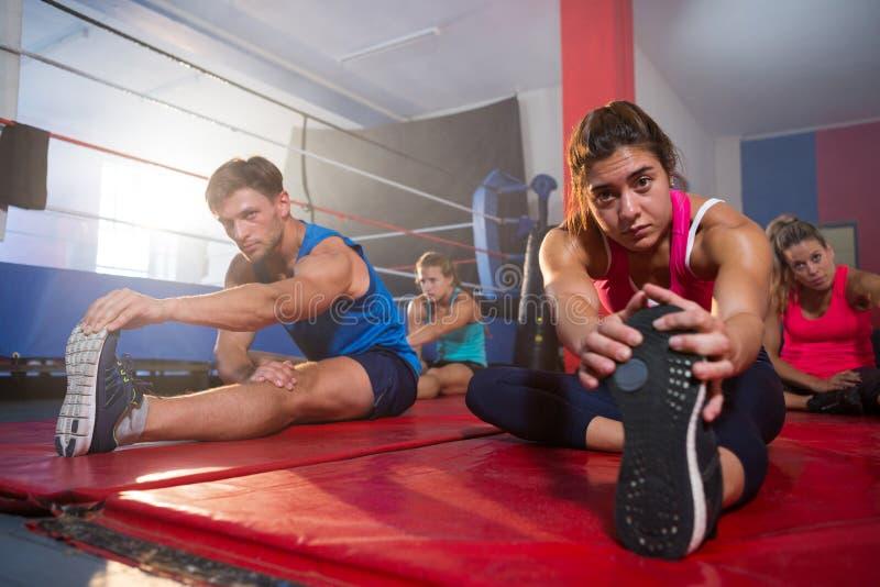 Atletas jovenes que practican ejercicio del estiramiento en las esteras imagen de archivo libre de regalías