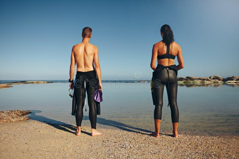Atletas jovenes que se colocan en la playa que se prepara para el triathlon fotografía de archivo