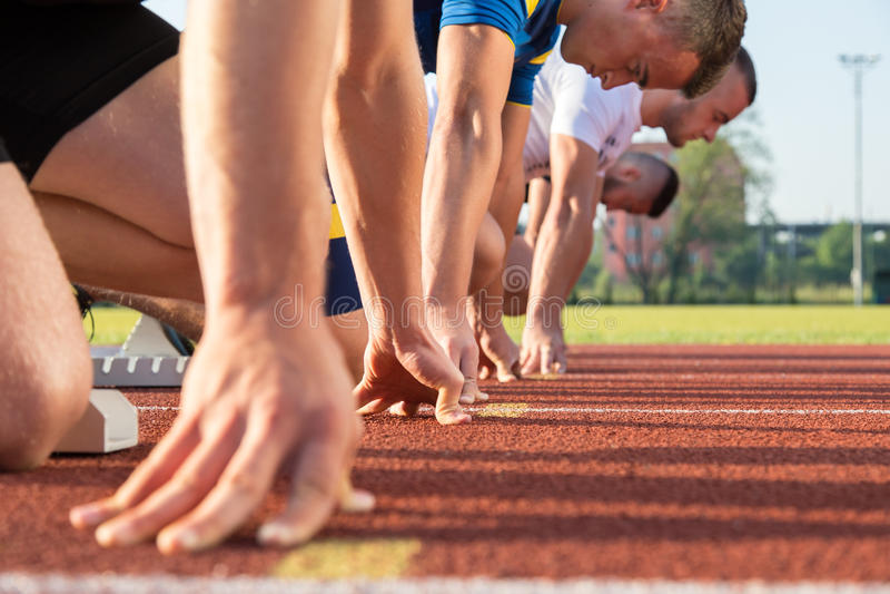 Atletas masculinos na linha de partida no dia ensolarado fotografia de stock