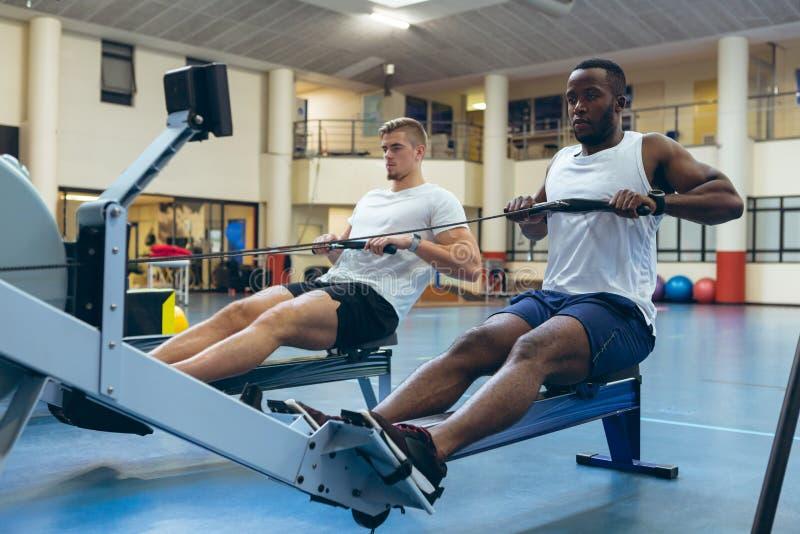 Atletas masculinos que exercitam com a máquina de enfileiramento no estúdio da aptidão foto de stock