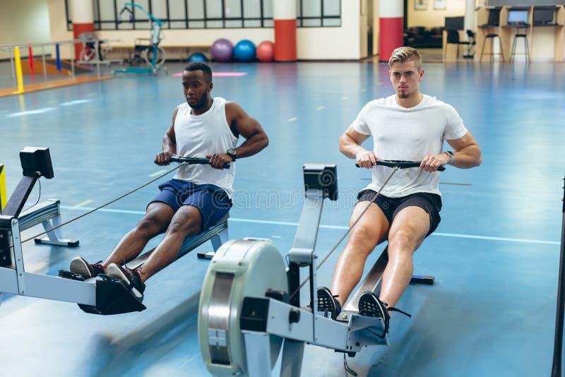 Atletas masculinos que exercitam com a máquina de enfileiramento no estúdio da aptidão fotos de stock royalty free