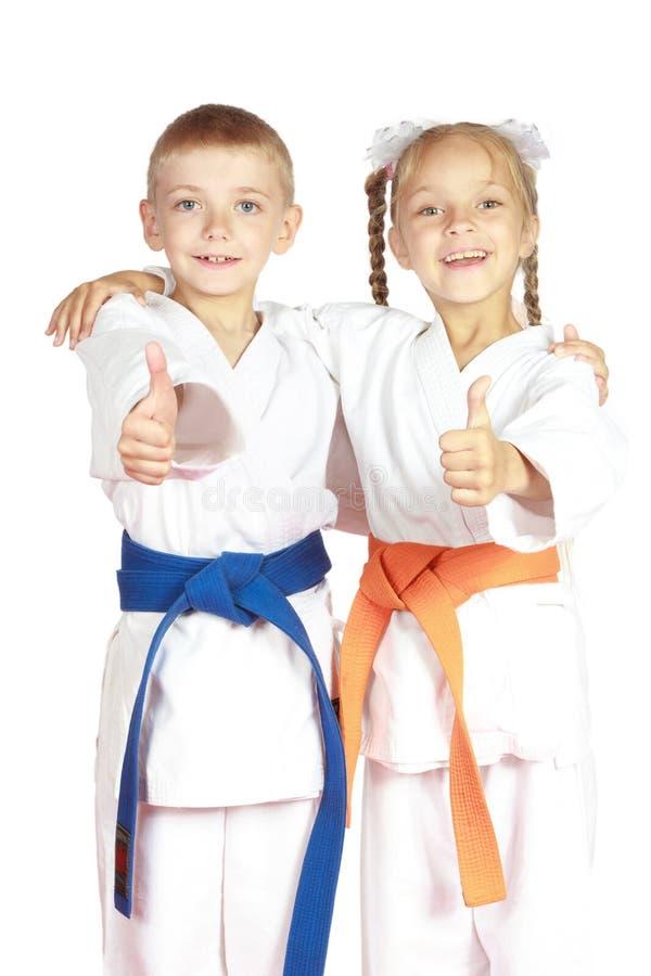Atletas muito felizes do menino e da menina no karategi fotografia de stock royalty free
