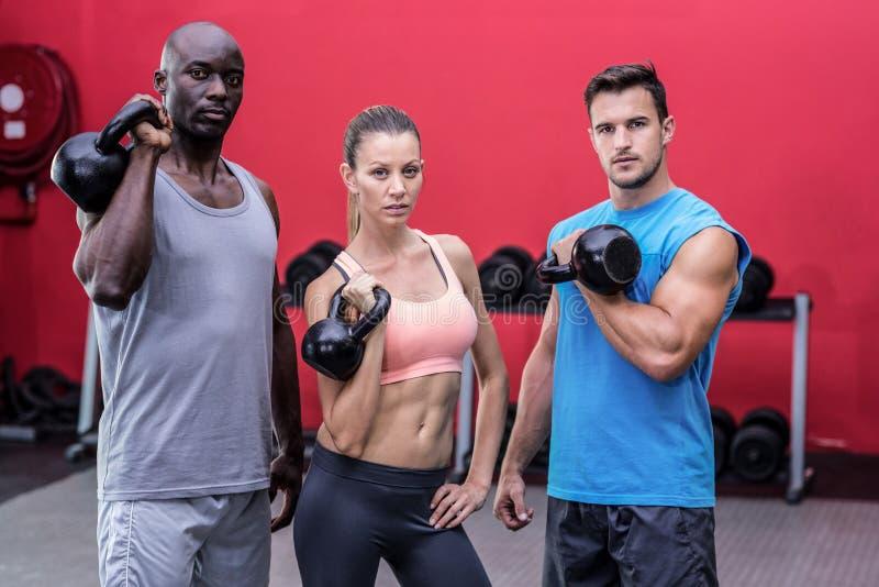 Atletas musculares serios que levantan kettlebells imagenes de archivo