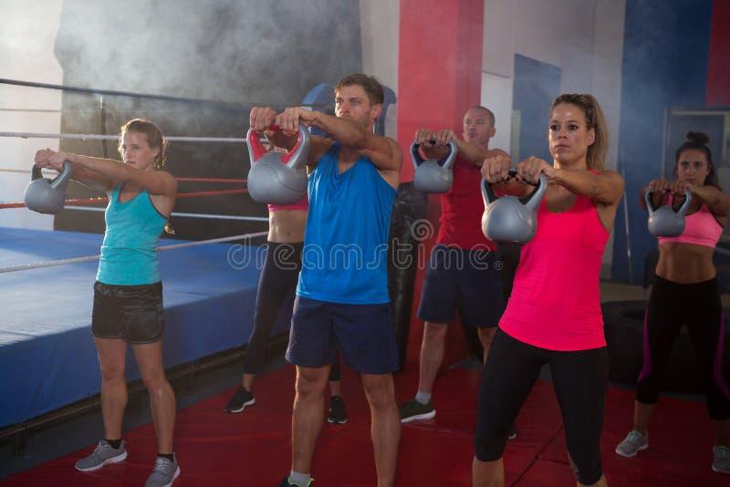 Atletas novos que exercitam com as chaleiras pelo anel de encaixotamento imagem de stock royalty free
