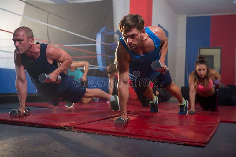 Atletas novos que exercitam com pesos pelo anel de encaixotamento imagem de stock royalty free