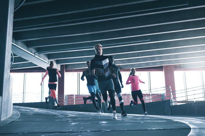 Atletas novos que treinam na terra de esportes imagens de stock royalty free