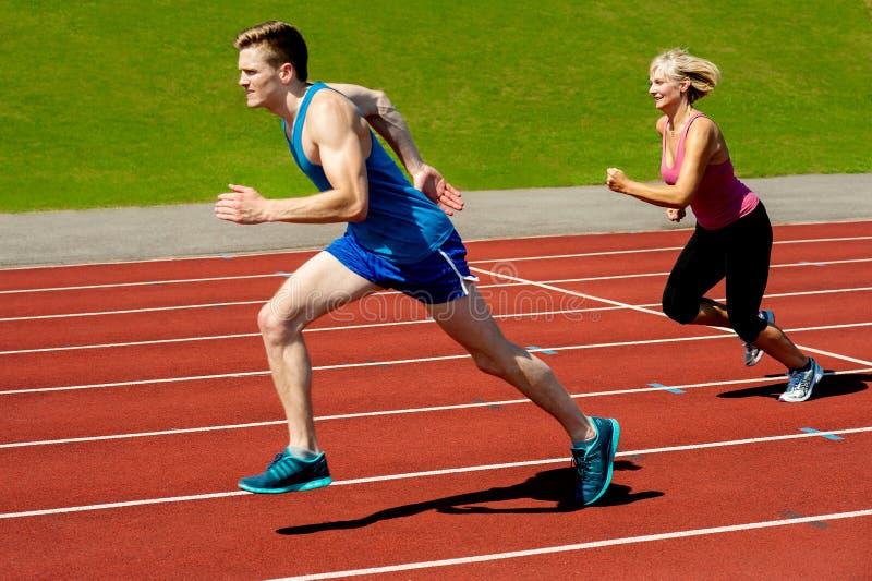 Atletas que corren en circuito de carreras foto de archivo libre de regalías