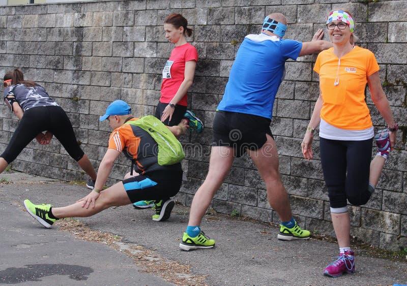 Atletas que hacen estirar ante la raza Devin Bratislava, Eslovaquia de 12 kilómetros foto de archivo libre de regalías