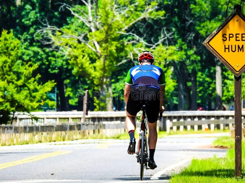 Atlete Cycling in Park voorbij een snelheidstop-bord royalty-vrije stock foto