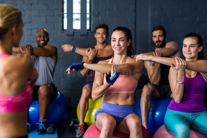 Atleten die terwijl het uitoefenen in gymnastiek glimlachen stock afbeeldingen
