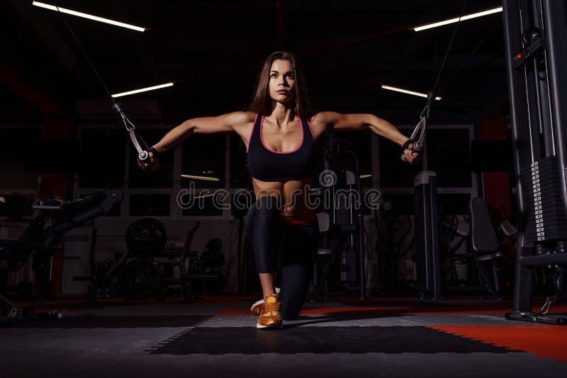 Atletenmeisje in sportkleding die en haar wapens en schouders met oefeningsmachine uitwerken opleiden in gymnastiek royalty-vrije stock fotografie