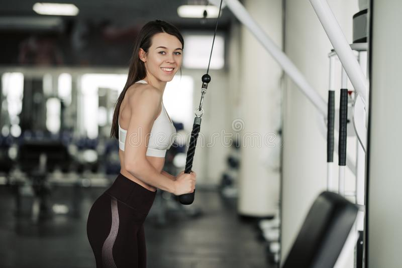 Atletenmeisje in sportkleding die en haar wapens en schouders met oefeningsmachine uitwerken opleiden in gymnastiek royalty-vrije stock foto