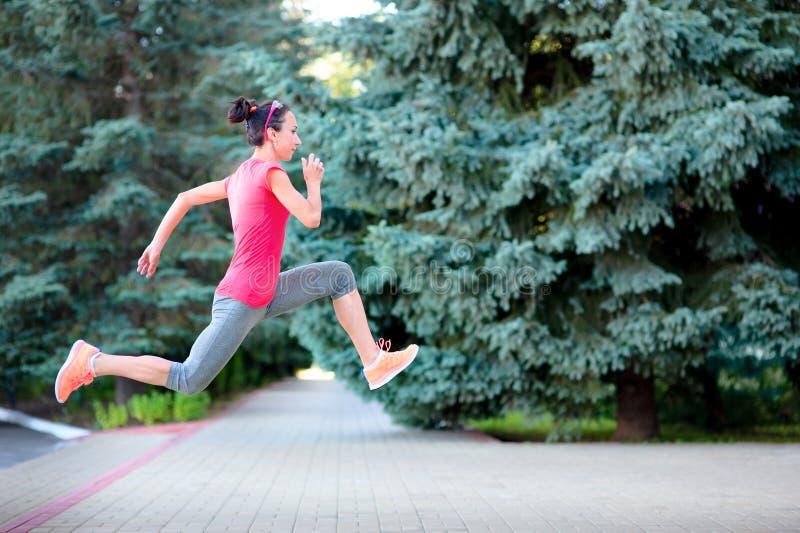 Atletenvrouw die en in opleiding lopen springen Vrouwelijke stedelijke athl royalty-vrije stock afbeeldingen