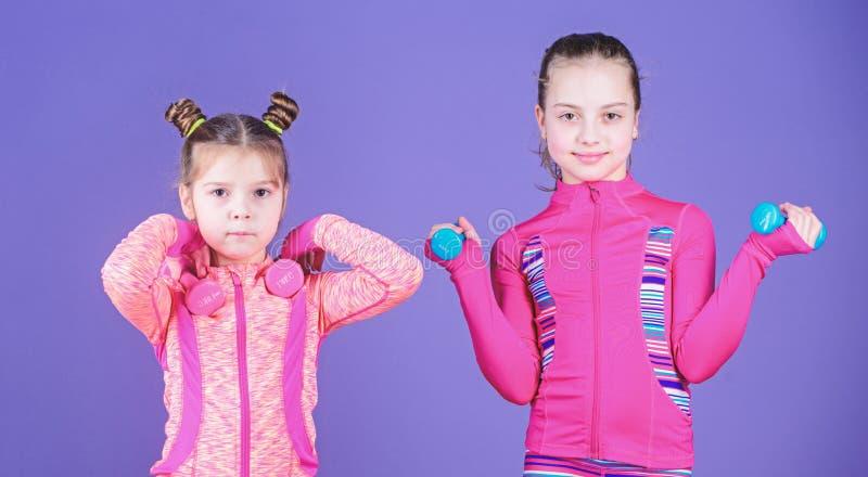 Atleti adorabili Piccolo bambini che sviluppano idoneit? fisica Le piccole ragazze godono dell'addestramento di forma fisica con  fotografia stock