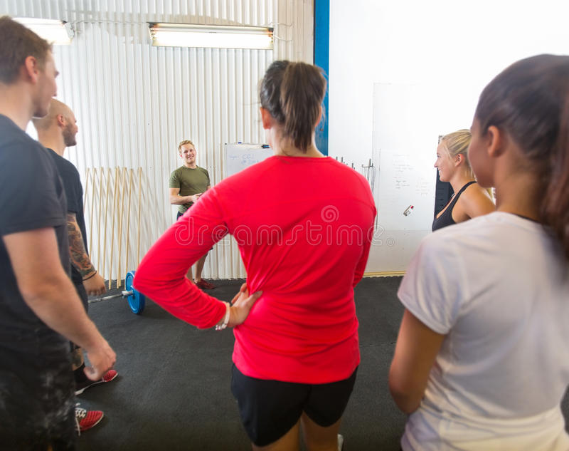 Atleti che ascoltano l'istruttore At Gym fotografie stock libere da diritti