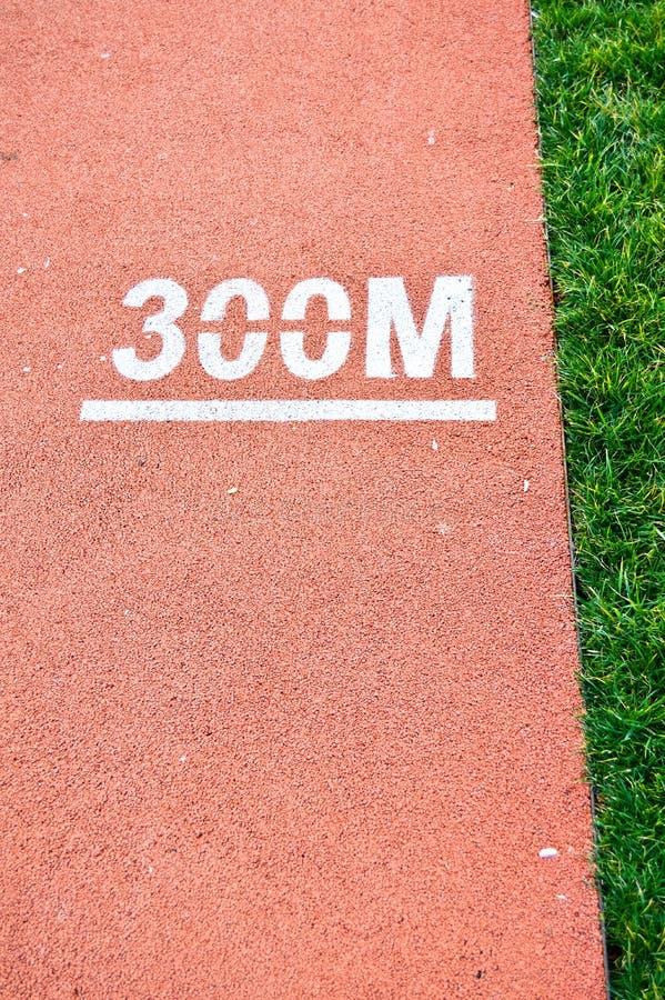 Atletica che esegue pista e le erbe in uno stadio Cominci, contesto immagini stock