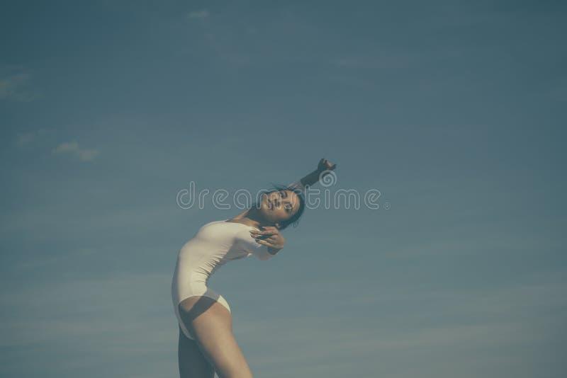 Atletico e flessibile Ballo di prestazione di concerto Giovane ballerina che balla sul cielo blu Danzatore di balletto sveglio Ra immagine stock