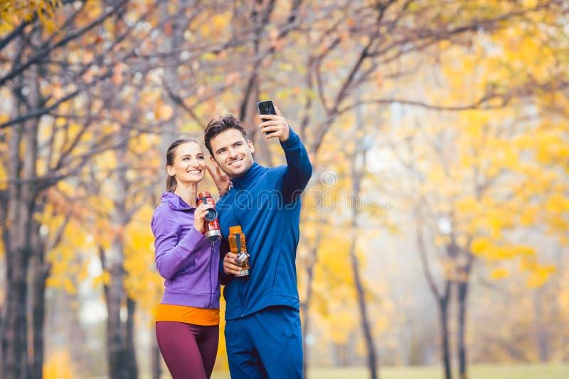 Atletisch geschiktheidspaar die selfie met hun telefoon voor sociale media nemen royalty-vrije stock foto's