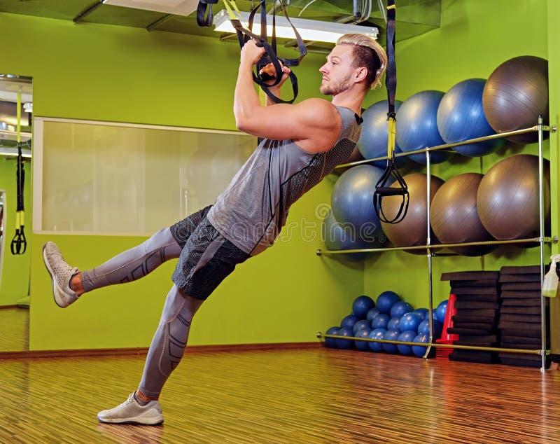 Atletisch mannetje die met trxriemen uitoefenen in een gymnastiekclub royalty-vrije stock foto's