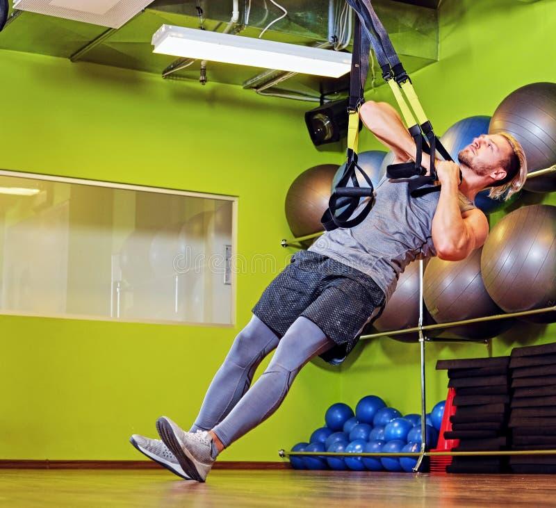 Atletisch mannetje die met trxriemen uitoefenen in een gymnastiekclub royalty-vrije stock fotografie