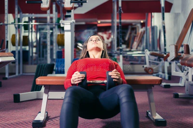 Atletisch meisje belast met geschiktheid vrouw die oefening met domoor op de bank doen royalty-vrije stock foto's