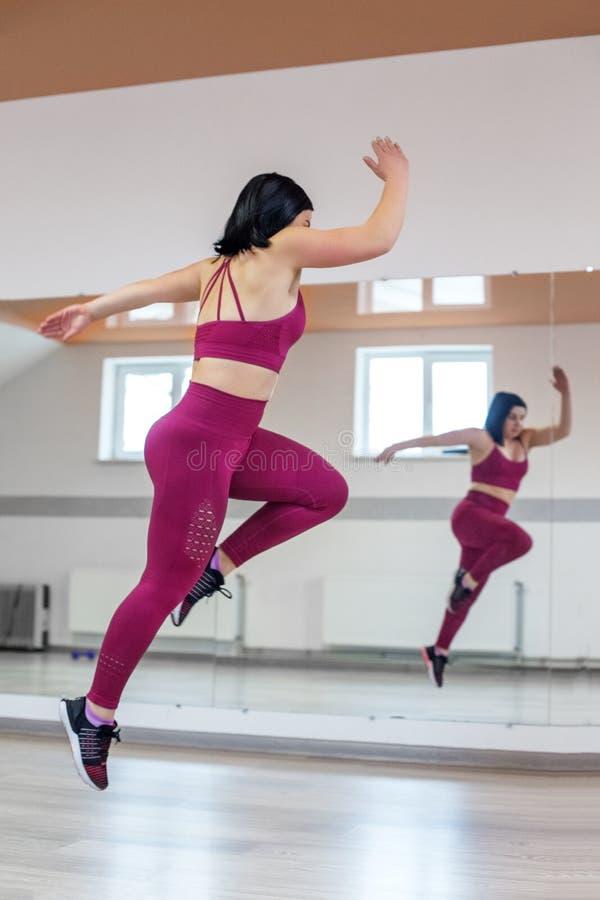 Atletisch meisje die in de gymnastiek springen Het concept sporten, een gezonde levensstijl, verliezend gewicht stock afbeeldingen