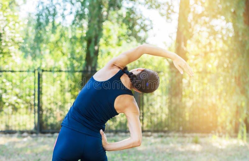 Atletisch meisje die in een park uitwerken Mooie in reliëf gemaakte rug stock afbeeldingen