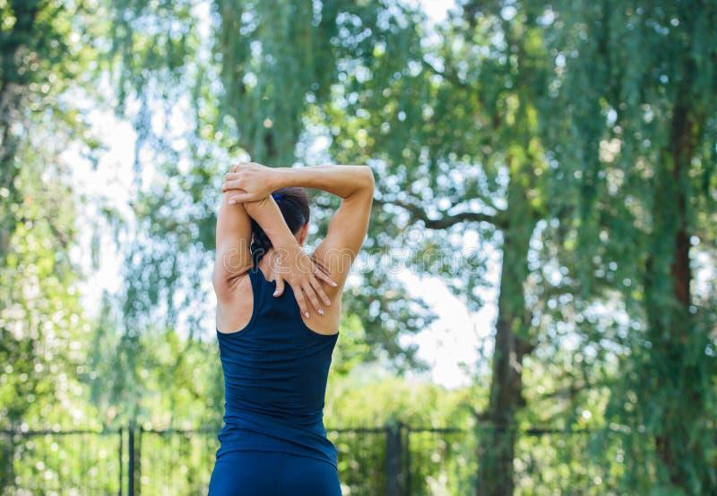 Atletisch meisje die in een park uitwerken Mooie in reliëf gemaakte rug royalty-vrije stock afbeeldingen