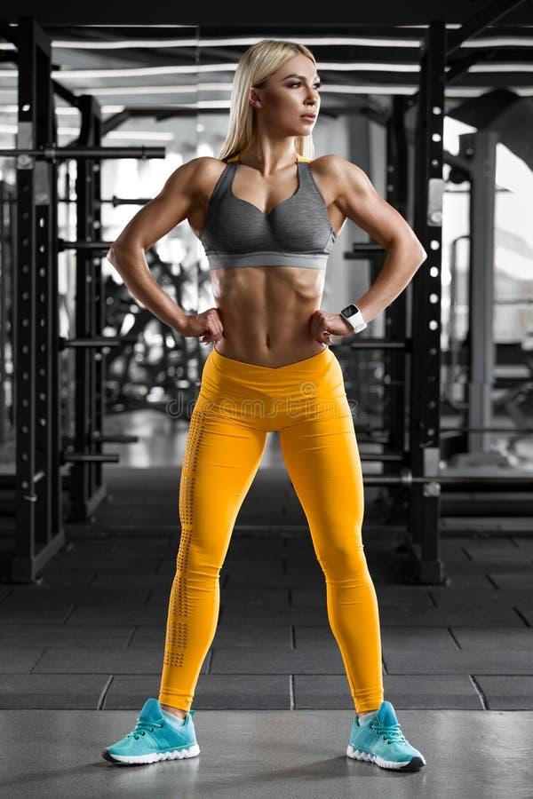 Atletisch meisje in gymnastiek, het uitwerken Geschiktheidsvrouw die abs en vlakke buik, gevormd lichaam tonen stock fotografie