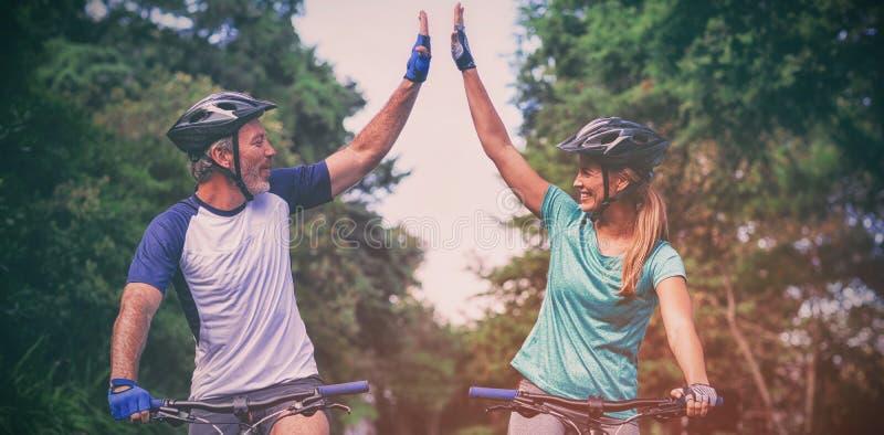 Atletisch paar die hoogte vijf geven terwijl het berijden van fiets op de weg stock foto's