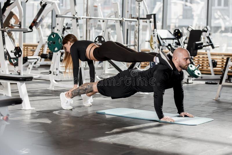 Atletisch paar die moeilijke sportoefening doen waar het meisje zich in de plank op een mens bevindt die zich binnen in de plank  royalty-vrije stock foto's