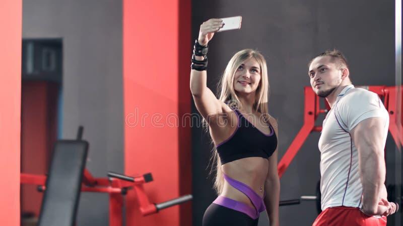Atletisch paar die selfies op de telefoon in de gymnastiek nemen stock foto's