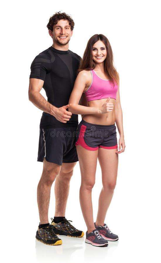 Atletisch paar - man en vrouw met duim omhoog op het wit stock foto