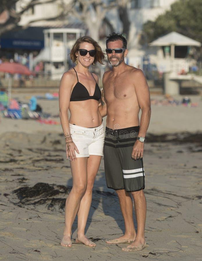 Atletisch paar op middelbare leeftijd in de zon op het strand stock afbeeldingen