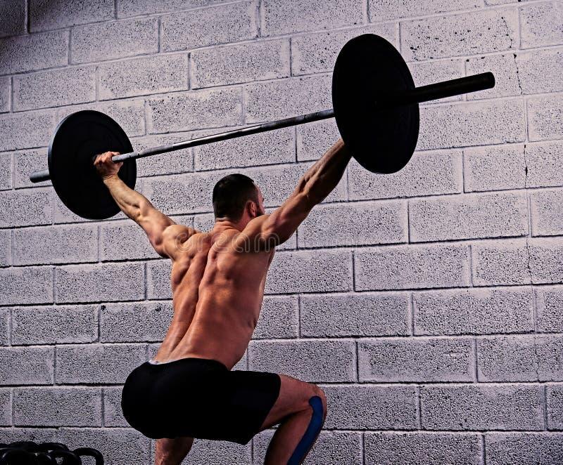 Atletisch shirtless mannetje die hurkzit met een barbell doen onder van hem hij stock afbeeldingen