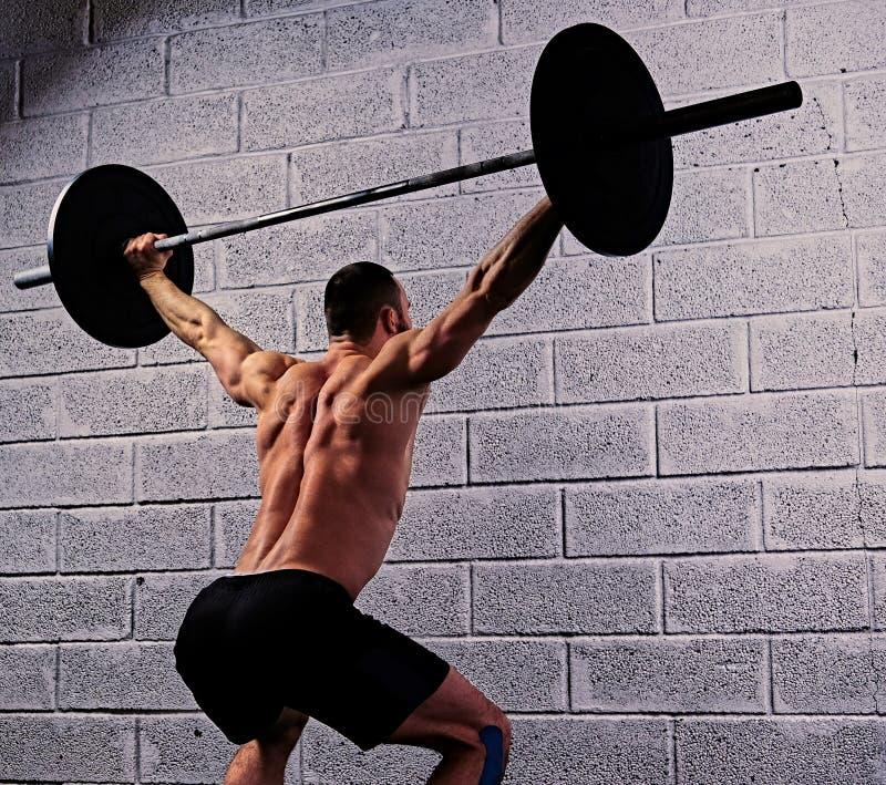 Atletisch shirtless mannetje die hurkzit met een barbell doen onder van hem hij stock fotografie