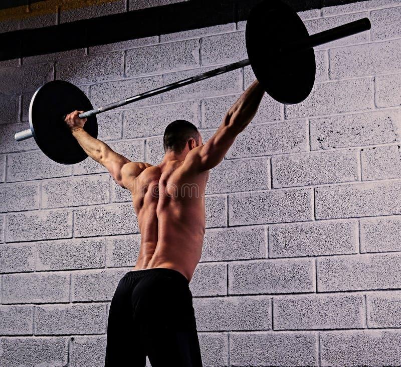 Atletisch shirtless mannetje die hurkzit met een barbell doen onder van hem hij stock foto