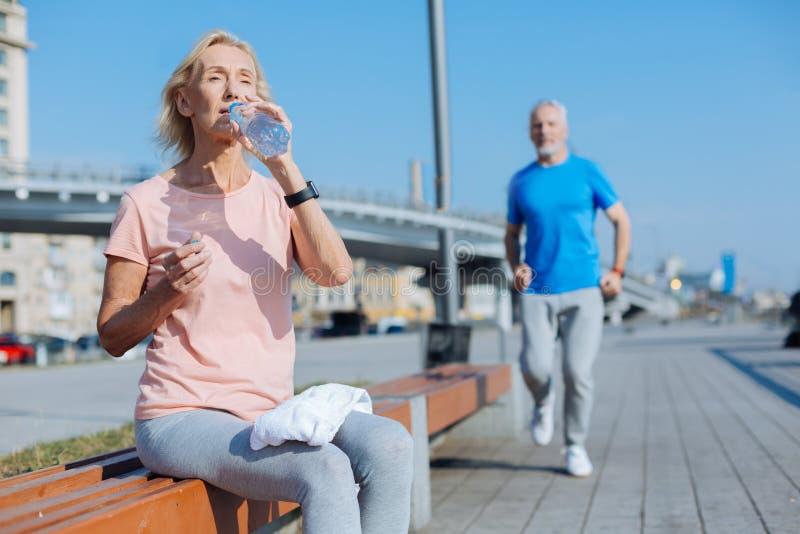 Atletisch vrouwen drinkwater na een ochtendlooppas stock fotografie