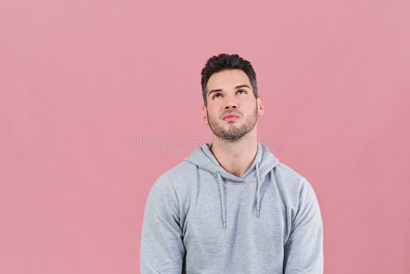 Atletische aantrekkelijke mens in een hoodie die omhoog met weemoedige het opherinneringen halen uitdrukking kijken Concepten keu royalty-vrije stock afbeelding