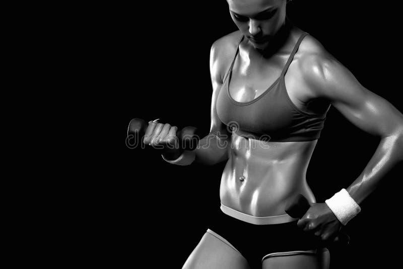 Atletische bodybuildervrouw met domoren meisje met spieren stock foto's