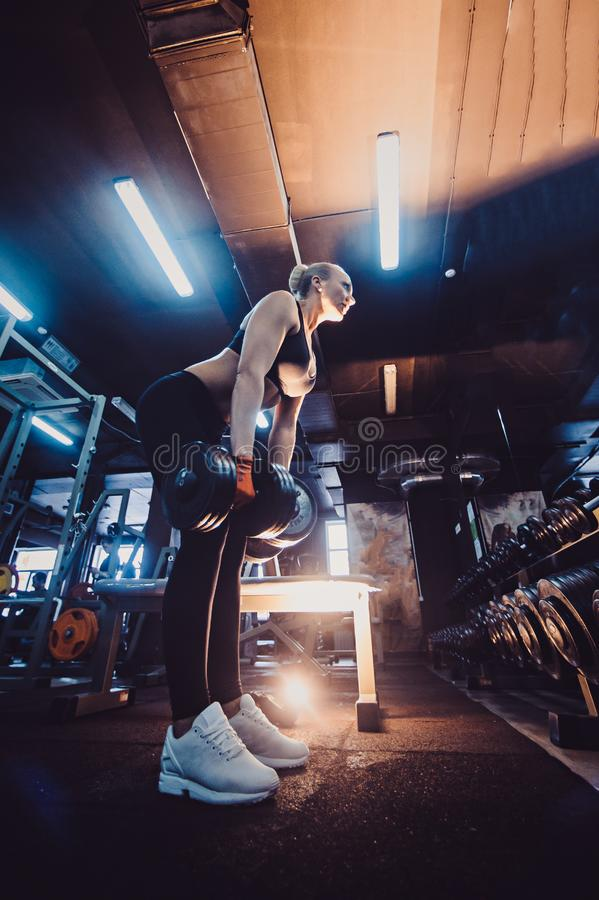 Atletische bodybuildervrouw met domoren mooi blondemeisje met spieren Gymnastiek stock fotografie