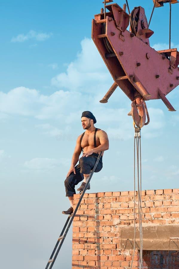 Atletische bouwer die op bakstenen muur leunen stock afbeelding