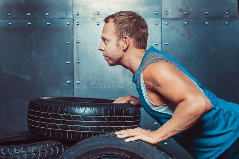 Atletische die mensentreinen, van een toekomstgerichte autoband worden geduwd concept gezondheid en sterkte stock fotografie