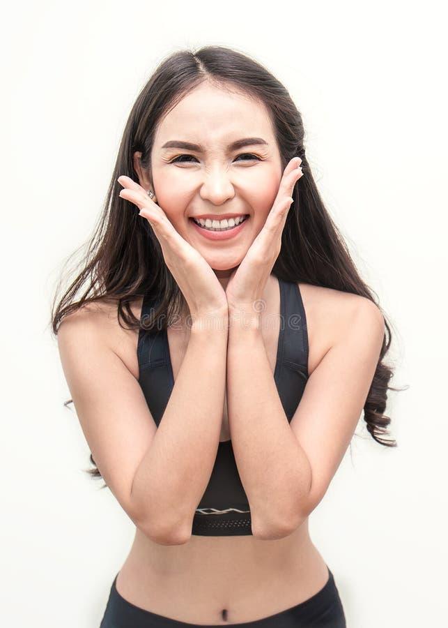 Atletische jonge Aziatische vrouw die met haar handen glimlachen die haar gezicht houden royalty-vrije stock foto's