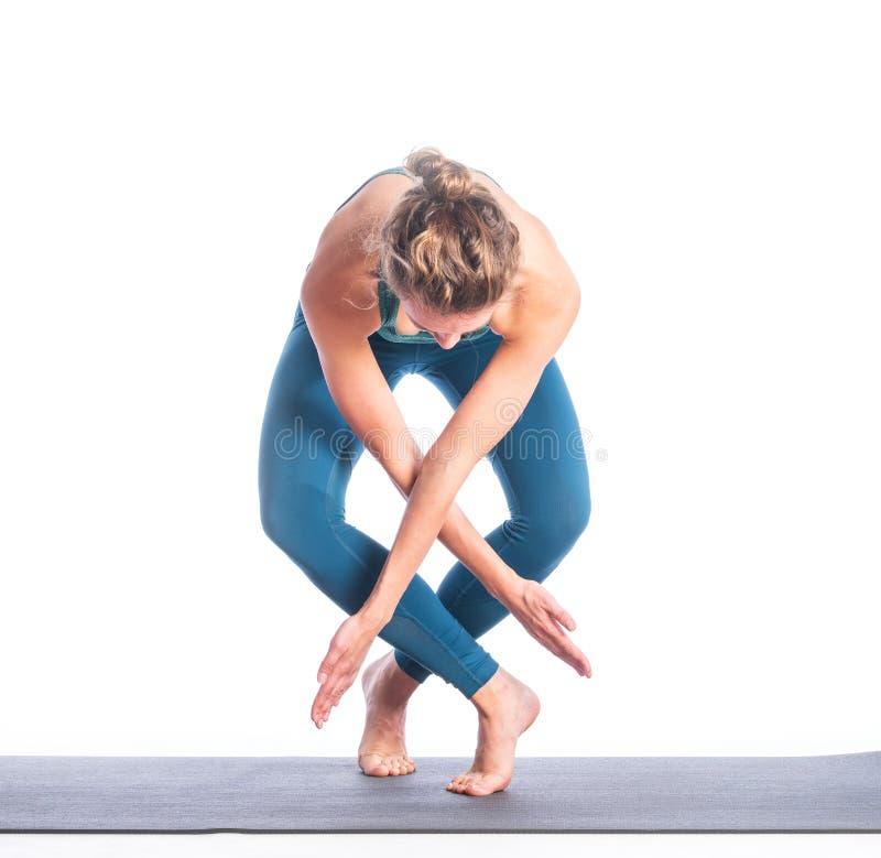 Atletische jonge blondevrouw die die yogapraktijk doen op witte achtergrond wordt geïsoleerd stock foto