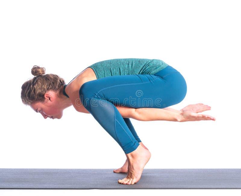 Atletische jonge blondevrouw die die yogapraktijk doen op witte achtergrond wordt geïsoleerd stock fotografie