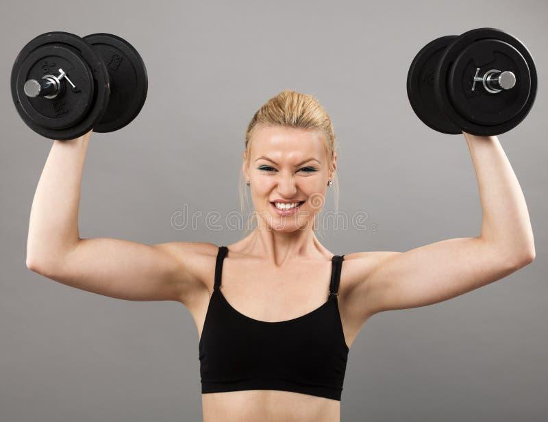 Atletische jonge dame die met gewichten uitwerkt royalty-vrije stock foto