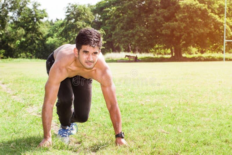 Atletische jonge mens die in de sportengrond lopen Gezond levensstijl, fitness en sportenconcept stock afbeelding